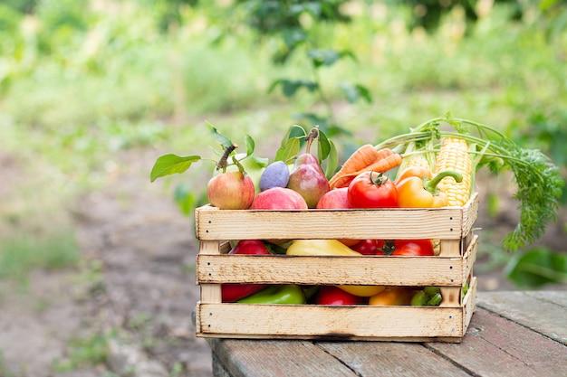 Деревянный ящик свежих фермерских овощей и фруктов на деревенском столе на открытом воздухе. концепция эко еды
