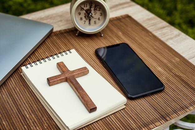 スマートフォンの横にある木製の十字架とノートブック。