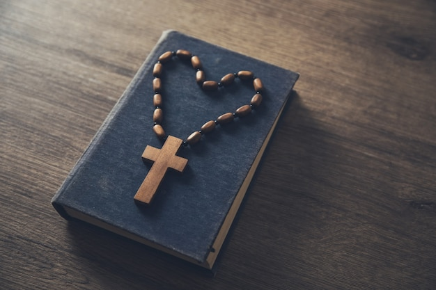 Wooden cross on the bible on the table