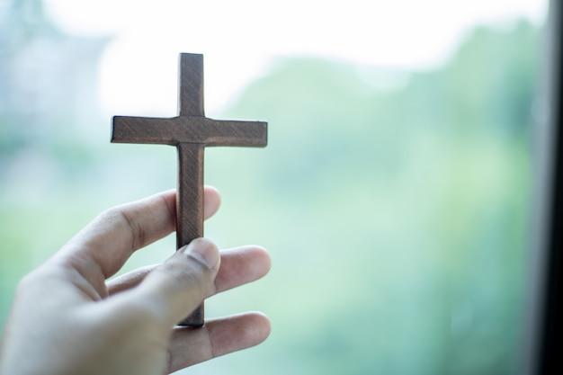Wooden cross on blurred bokeh background.