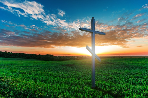 Wooden cross in morning green field. christian concept