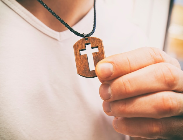 Wooden cross necklace on man's neck