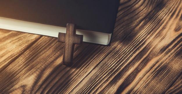 木製のテーブルの上の聖書の木製の十字架