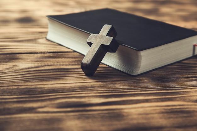 Деревянный крест на библии на деревянном