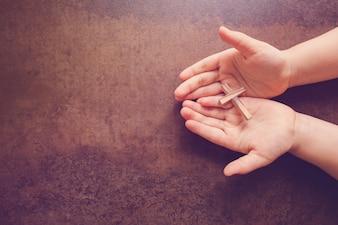 Wooden cross on praying children hands