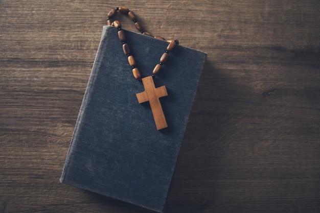 Деревянный крест на библии на столе