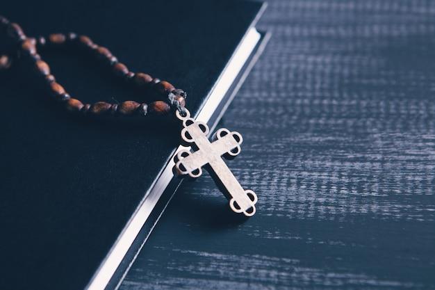 木製のテーブルの上の本の木製の十字架