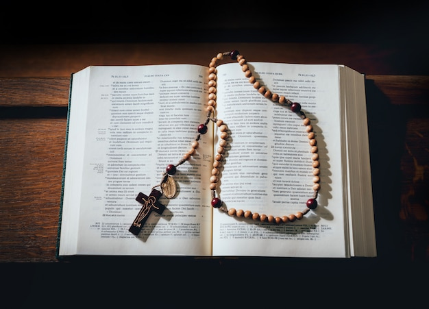 The wooden cross over opened bible on wooden table