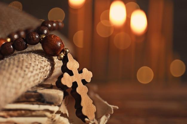 Wooden cross on sackcloth against defocused lights