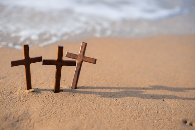 A wooden cross on the sand on the beach.
