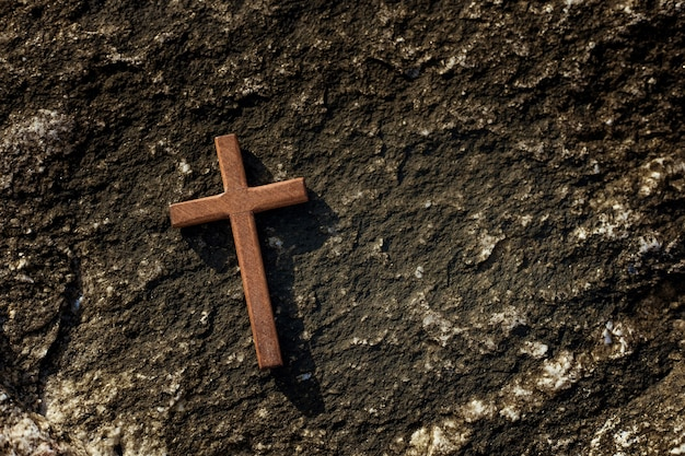 Wooden cross on stones background.