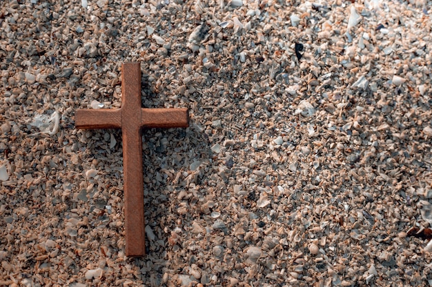 Wooden cross on stones background.