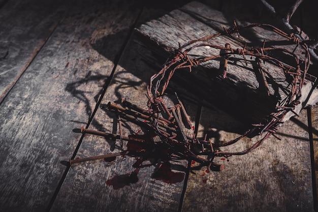 いばらの冠と暗い背景に血まみれのスパイクと木製の十字架