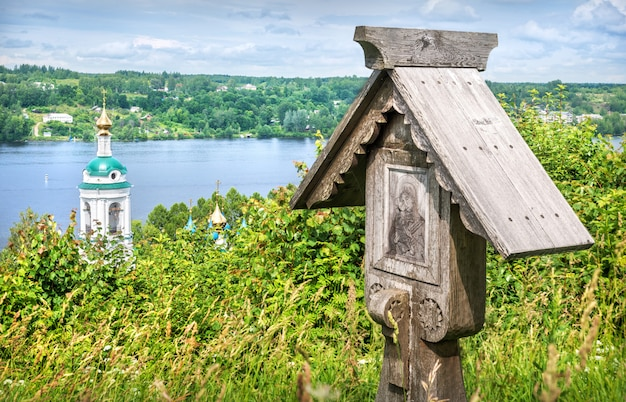 Wooden cross with the image of the mother of god and the bell tower of the varvarinskaya church overlooking the volga river in plyos on a summer sunny day