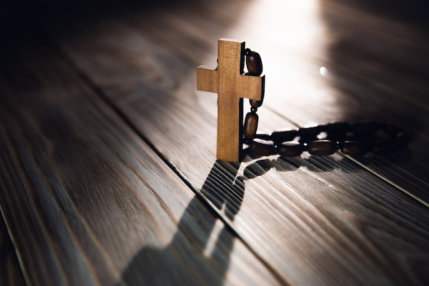 Wooden cross with necklace on the table