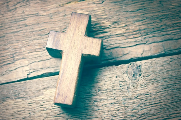 Wooden cross on the wooden table background