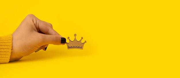 노란색 배경 위에 손에 나무 왕관, 왕, 여왕의 힘에 대 한 개념.