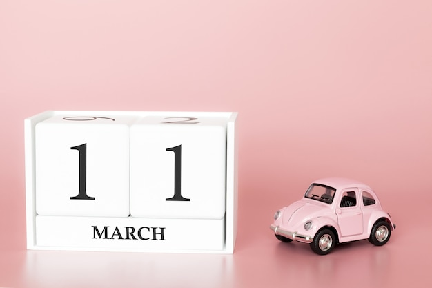 Wooden cube 11th of march. day 11 of march month, calendar on a pink background with retro car.
