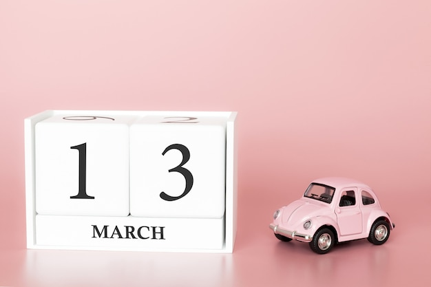 Wooden cube 13th of march. day 13 of march month, calendar on a pink background with retro car.