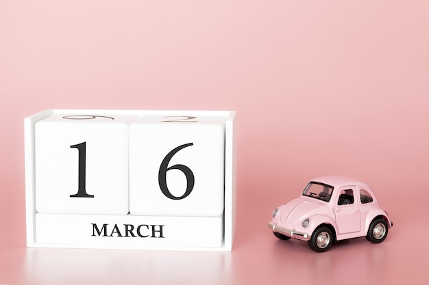 Wooden cube 16th of march. day 16 of march month, calendar on a pink background with retro car.