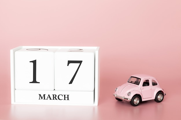 Wooden cube 17th of march. day 17 of march month, calendar on a pink background with retro car.