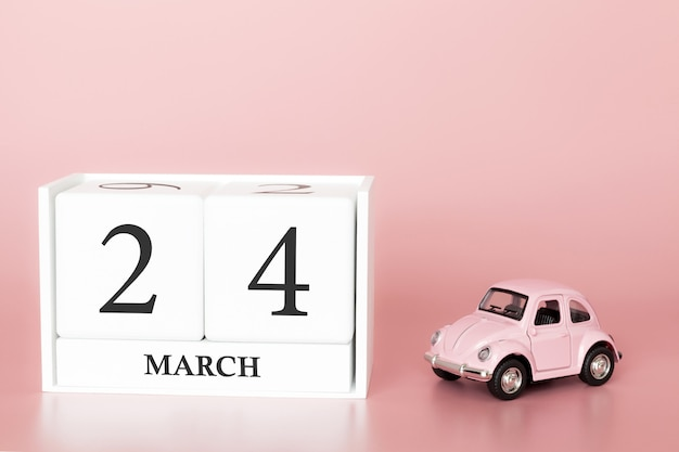 Wooden cube 24th of march. day 24 of march month, calendar on a pink background with retro car.