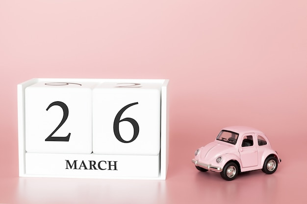 Wooden cube 26th of march. day 26 of march month, calendar on a pink background with retro car.