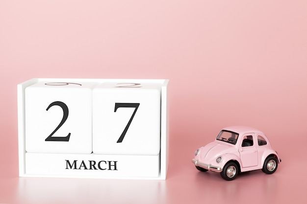 Wooden cube 27th of march. day 27 of march month, calendar on a pink background with retro car.