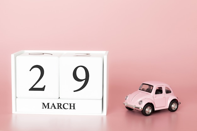 Wooden cube 29th of march. day 29 of march month, calendar on a pink background with retro car.