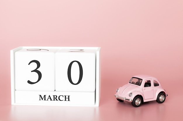 Wooden cube 30th of march. day 30 of march month, calendar on a pink background with retro car.