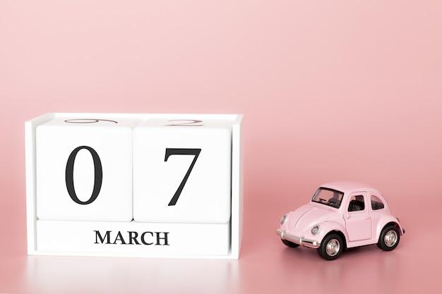 3月7日の木の立方体。 3月の7日目、レトロな車とピンクの背景のカレンダー。