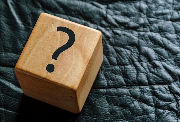 Wooden cube on black leather with question mark