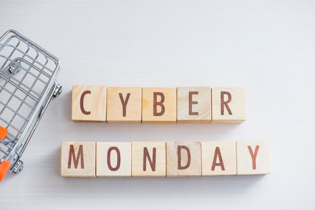 Wooden cube block cyber monday word on table with mini shopping cart.