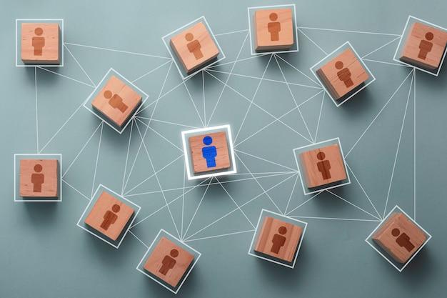 組織構造のソーシャルネットワークとチームワークの概念の接続ネットワークをリンクする木製キューブブロック印刷画面人アイコン。