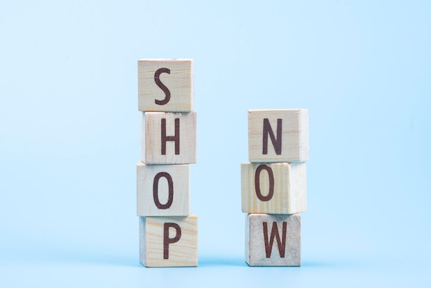 Wooden cube block shop now word on blue