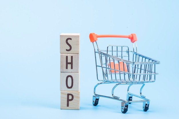 Wooden cube block shop word with mini shopping cart on blue