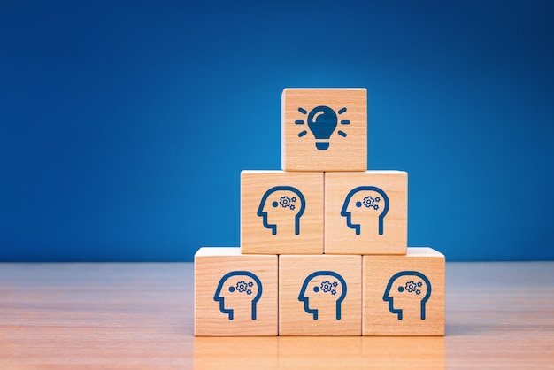 Wooden cube block with head human symbol and light bulb.teamwork it's an easy way to resolve problem. concept creative idea.