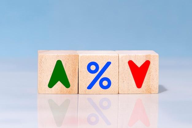 Деревянный кубический блок с иконкой в процентах, стрелкой вверх и вниз. концепция процентных финансовых и ипотечных ставок.