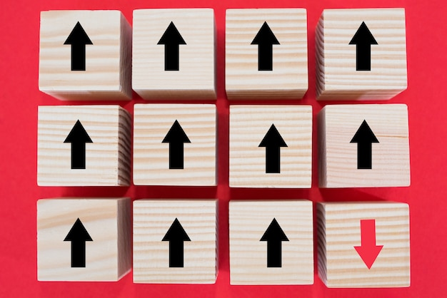 Wooden cube block with a red arrow pointing in the opposite direction from the rest of the cubes