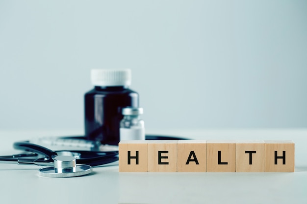 Wooden cube block with word healh and medical equipment on table. insurance and healthcare concept