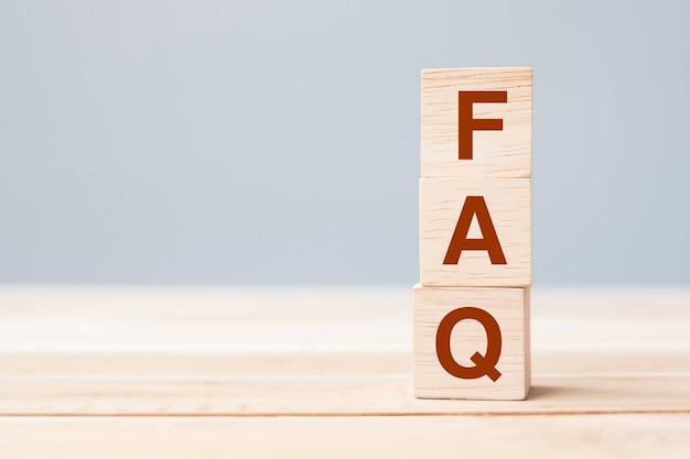 테이블 배경에 faq 텍스트(자주 묻는 질문)가 있는 나무 큐브 블록. 금융, 마케팅 및 비즈니스 개념