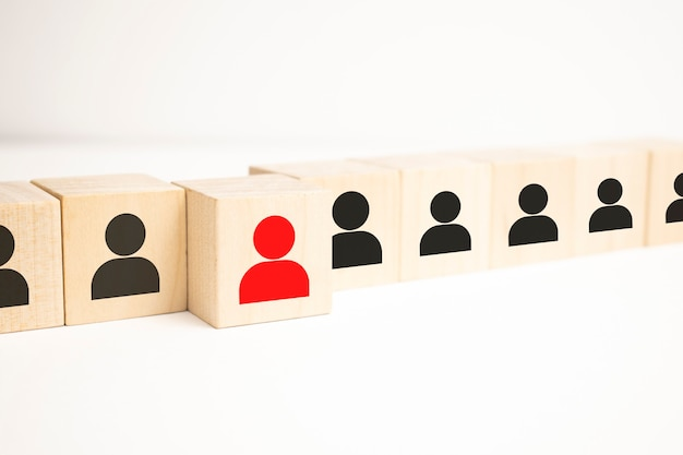Wooden cube blocks with icon people standing out from the crowd with a woman leader in red.