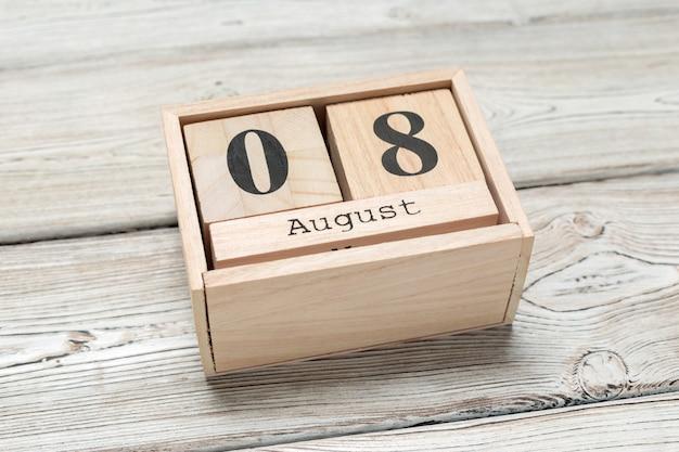 Wooden cube shape calendar for aug 8 on wooden