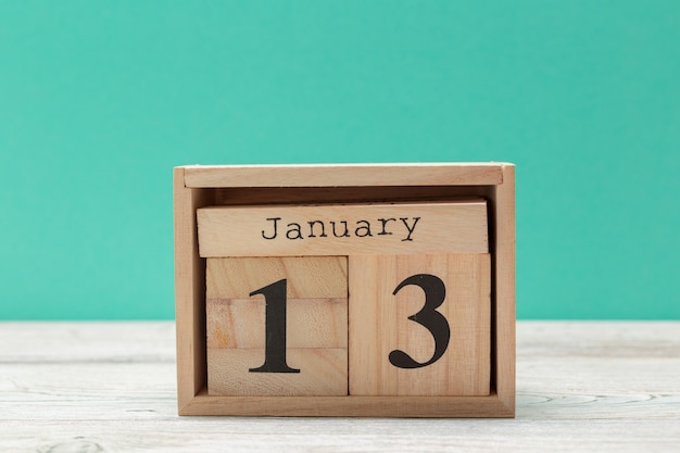 Wooden cube shape calendar for january 13 on wooden tabletop