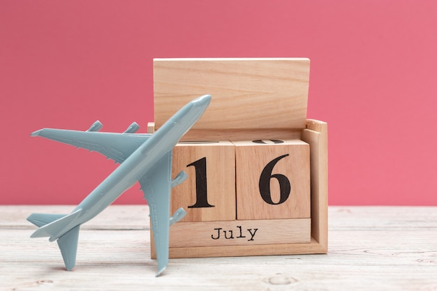 Wooden cube shape calendar for july 16 on wooden tabletop