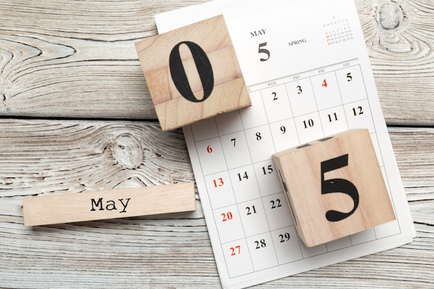 Wooden cube shape calendar for may 5 on wooden