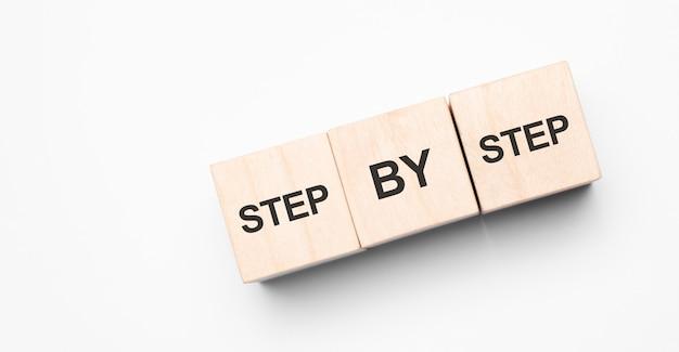 ステップバイステップの単語と木製の立方体のスタック。ビジネスにおけるリーダーシップ、成功、勝利の概念