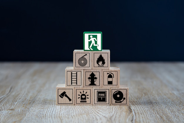 Wooden cube stacked in pyramid shape with fire and safety icons.