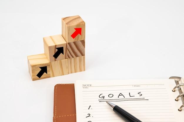 Деревянная кубическая лестница со списком целей и стрелками, бизнес-концепция целей и успеха