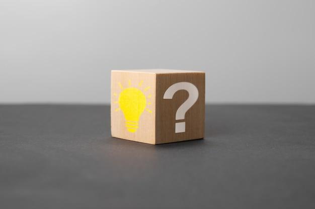 明るい電球と黒いテーブルに疑問符が付いた木製の立方体。創造的なアイデア、イノベーション、ソリューションのコンセプト。電球のアイコンと疑問符の記号が付いた木製の立方体。コピースペース